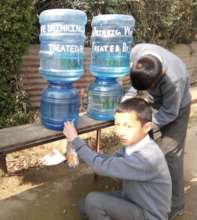 Children using jar and dispenser for water