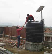 Students on the roof of the school adding WATAsol