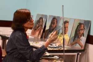 Artist Cindy Catotti with her portraits