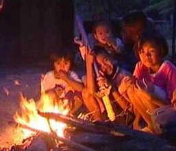 Children sit around litted flame to keep warm