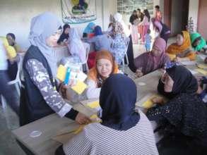 Volunteer Hameda (blue scarf) assisiting workshop