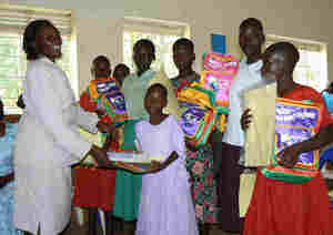 Program officer handing over scholastic materials