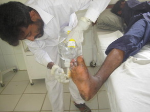 Technician cleaning a patient's foot