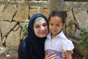 Malak, 5 years old, with her teacher Fawz.