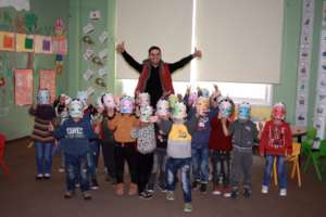Teacher Mahmoud and students roar in lion masks.