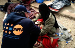 A UNFPA staff member speaking with a mother.