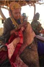 Inaden artisan Tibilan Ana sewing an adefur pillow