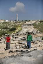 Youth standing on demolished road to Aqaba