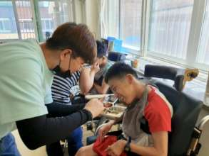 Minyeal helping to feed a young adult at Aemangwon
