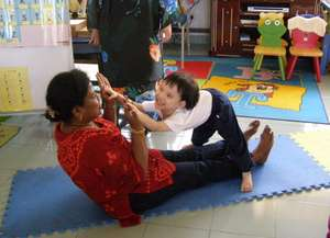 Ms. Jaya playing with a kid during a home visit