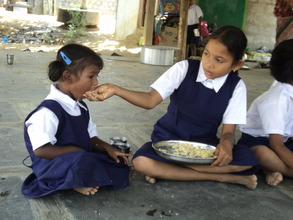 A girl feeding her small sister in BASS school