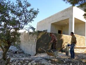Sadeq and friend plastering the porch he added on