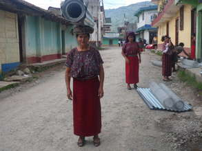 Ixil woman carries materials for her chicken coop
