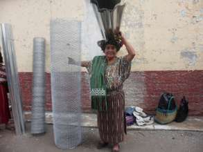 An Ixil woman with supplies for her chicken coop