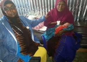 Sahara holds her newborn, Fatima