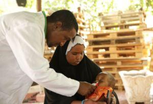 Abdi checks the health of a newborn