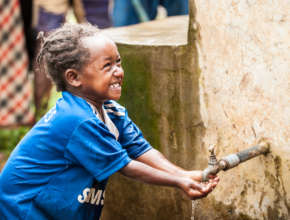 A young girl washes her hands with the clean water