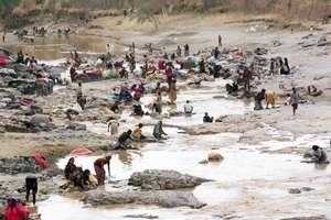 Villagers gather to collect water
