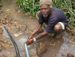 A man cleans his hands with fresh water