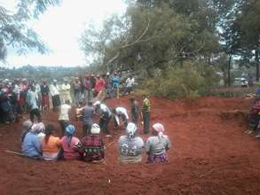 Parents volunteering to excavate a water tank foundation for their children.jpg