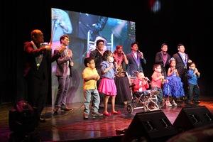 Pauline in blue Princess gown sings on-stage