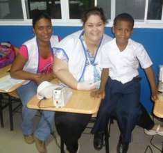 Audiologists Aixa and Ivis with a school boy