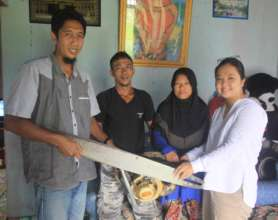 Herwandi, his wife, and Monica with his chainsaw