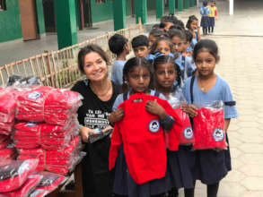 Ineke Zondag giving out winter clothes to children