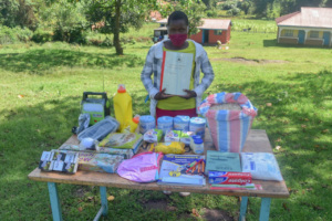 An eighth grader with her Angaza care package