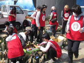 Volunteers placing candles in bamboo holders