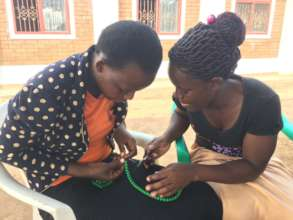 Young mothers learning jewelery making skills