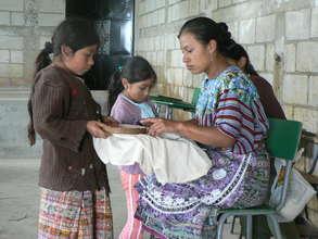 Intern teaching girls sewing skills