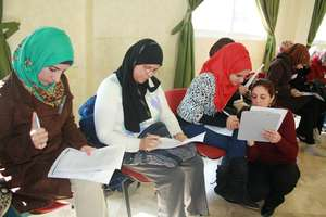 Suhad helps a participant with her self-evaluation
