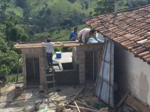 Community members assist with building latrines