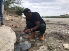 Taking a water sample from a drinking water puddle