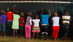 Learners draw on chalkboard wall in new classroom